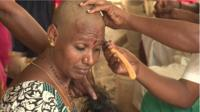 A woman in India having her head shaved