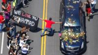 Well-wishers touch the hearse carrying the body of the late boxing champion Muhammad Ali