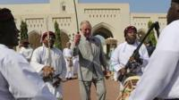 Prince Charles dances with a sword with a group of Omani traditional dancers in Muscat, Oman