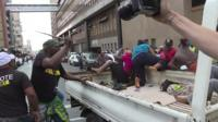 ANC supporters - one of them wielding a stick - are seen chasing away Black Land First activists