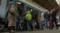Migrants board a train in Budapest