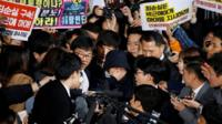 Choi Soon-sil surrounded by media and protesters