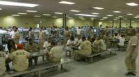 Hundreds of prisoners crammed in one single room for sleeping and eating.