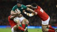 Two Welsh players tackling an Ireland player