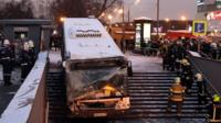 Firemen gather around a crashed bus by the entrance of a pedestrian underpass in Moscow