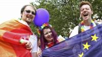 People hold an European Union flag as they take part in the annual Pride London Parade