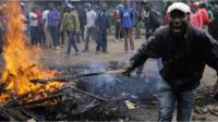 A protester in Nairobi light a stick on fire