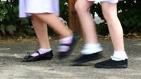 The legs and feet of two school girls walking