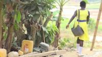Ghanaian schoolgirl walking across river