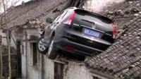 Car stuck in roof of house in China