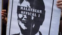 """Protester's sign, with an image of Najib Razak with his eyes blacked out by text reading """"Malaysian Official 1"""""""
