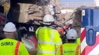 Workmen removing debris