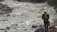 A rescue worker looks at a river