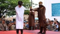 Man in white gown getting caned in front of a crowd