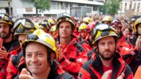 Firefighters joined the crowds in solidarity while Spanish police look on.