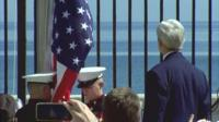 John Kerry looks on at US flag