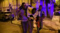 Migrants helping injured man