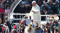 Pope Francis waves from the popemobile on his way to the cathedral, in Mexico City.