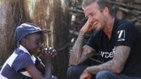 A child laughs with David Beckham