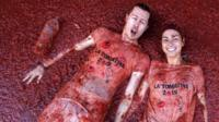 Revelers lie in tomato pulp