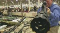 Man holding a gun for sale at a US gun show