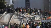 เจ้าหน้าที่หน่วยกู้ภัยและอาสาเร่งค้นหาผู้รอดชีวิตที่ติดอยู่ ใต้ซากอาคารที่พังถล่มลงมาหลังเหตุแผ่นดินไหว