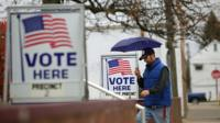 A man with umbrella walks past voting signs displayed outside a polling station during the mid-term elections
