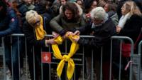 Women hang a yellow ribbon