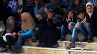 People, who were evacuated from the two rebel-besieged Shiite villages of Foah and Kefraya, wait at insurgent-held Rashidin, to travel to government-controlled Aleppo
