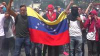 Anti-government protesters in Caracas wave a Venezuelan flag