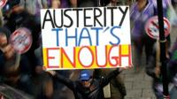 A protester with a placard that reads austerity that's enough