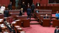Green Party senators walk out as Australia's One Nation party leader Pauline Hanson (right) makes her maiden speech