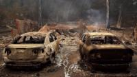 Charred cars parked in front of destroyed home in Northern California.