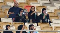 Veiled girls use their phones in a football stadium