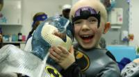 William holds his Batman mask