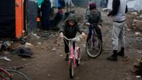 Afghan children ride their bicycles in a makeshift migrants camp near Calais.