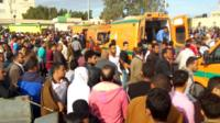 People gather around ambulances after the attack at the Rawda mosque on 24 November
