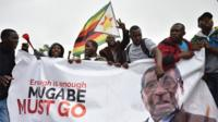 "People wave a Zimbabwean national flag and carry banners during a demonstration demanding the resignation of Zimbabwe""s president on November 18, 2017 in Harare."