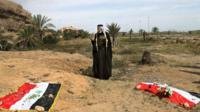 Man prays for his relative at mass graves site in Iraq