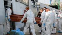 A coffin is carried out of the Italian Navy ship Bettica, at the Sicilian Porto Empedocle harbor, Italy.