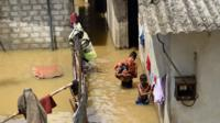 Sri Lankan youths wade through floodwaters