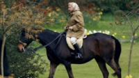 The Queen riding a horse in the grounds of Windsor Castle