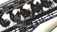 Rescue workers are seen next to people stuck in the Arkham Asylum roller coaster ride at the Warner Bros. Movie World theme park in Gold Coast, Australia