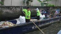 People cleaning up a canal in Bangkok