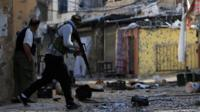 Palestinian gunmen from the Fatah faction attempt to cross a street during clashes in the Ein el-Hilweh refugee camp in Lebanon on 10 April 2017