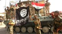 Shiite fighters and Iraqi security forces hold an Islamic State flag in Saqlawiya, north of Falluja, Iraq