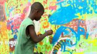 An artist boy painting in Ghana's capital, Accra