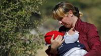 A Syrian migrant woman, holding a baby, on the Greek island of Lesbos