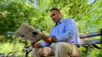 Naveed Jamali sitting on a park bench and reading a newspaper