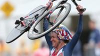 Kristin Armstrong holds up her bicycle